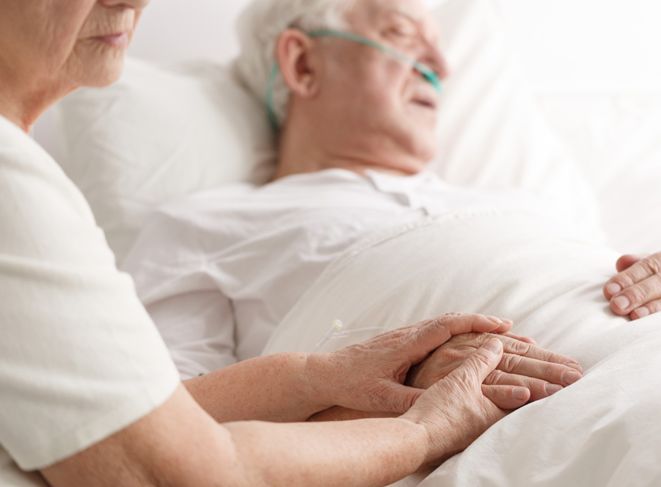 Elderly woman holding mans hand in hospital bed